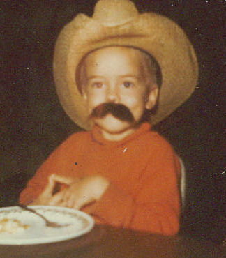 Me at four years old sitting at the dining table wearing a fake mustache and a cowboy hat (cowboy)
