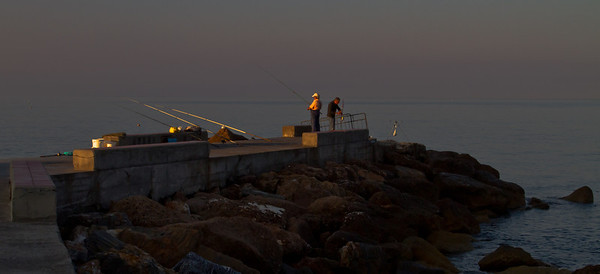 the very first rays of sunlight strike these early morning fisherman on the pier in Varigotti, Liguria, Italia