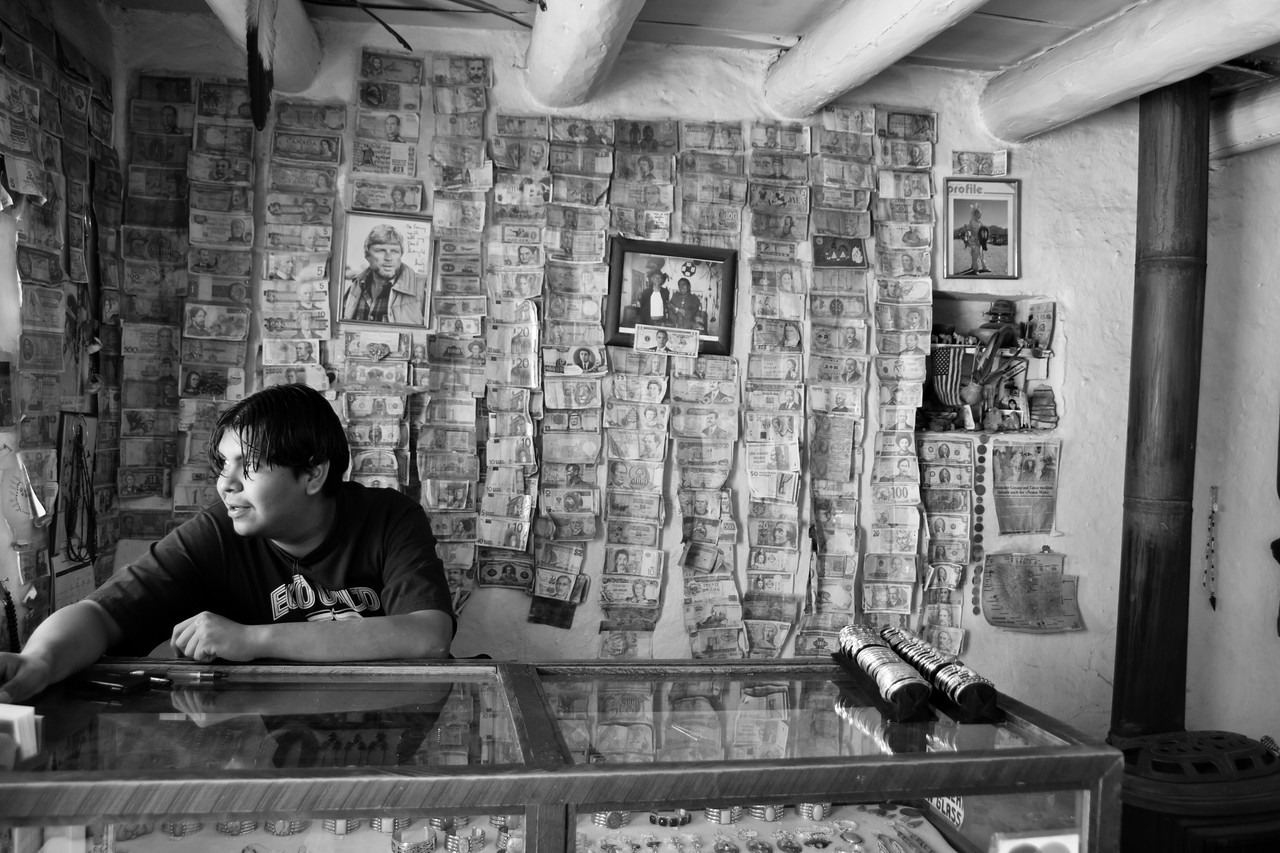 A young man tends the register in a store selling hand crafted jewelry in Taos Pueblo, the only living Native American community designated both a World Heritage Site by UNESCO and a National Historic Landmark.