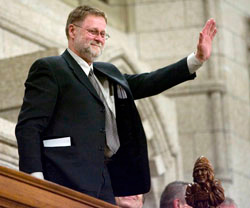 Canadian Press photographer Fred Chartrand acknowledges a standing ovation as he is recognized in the House of Commons by Speaker Peter Milliken for 38 years of exemplary service covering Parliament Hill and eight prime ministers, following Question Period in Ottawa Friday Feb. 29, 2008.  THE CANADIAN PRESS/Tom Hanson