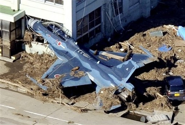 A Japanese military plane has its nose struck in a building at Matsushima air base of the Japan Air Self-Defense Force, northeastern Japan, on Saturday, March 12, 2011, one day after a giant quake and tsunami struck the country's northeastern coast. (AP Photo/Kyodo News)  MANDATORY CREDIT, NO LICENSING ALLOWED IN CHINA, HONG  KONG, JAPAN, SOUTH KOREA AND FRANCE