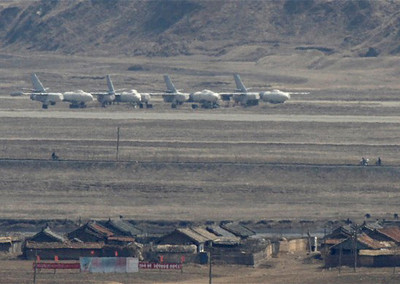 Residents ride their bicycles past Harbin H-5 bomber jets at Uiju Airfield near the North Korean town of Sinuiju, opposite the Chinese border city of Dandong, April 9, 2013. (Reuters Photo/Jacky Chen)