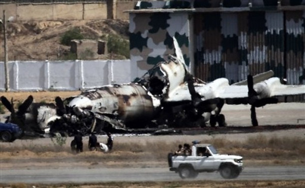 Pakistani troops drive past a wreckage of a gutted aircraft  at Pakistan Navy base  in Karachi, Pakistan on Monday, May 23, 2011. Pakistani commandos regained control of a naval base Monday from a team of Taliban militants who had attacked then occupied the high-security facility for 18 hours, dealing a bloody and humiliating blow to the military. (AP Photo/Shakil Adil)