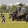 Military personnel inspect a Republic of Singapore Air Force (RSAF) AH-64 Apache helicopter as it sits in an open field after crash landing in the Woodlands area in northern Singapore September 30, 2010. Singapore's Ministry of Defence said the helicopter made a forced landing in the field, and the pilots appeared uninjured, local media reported. REUTERS/Vivek Prakash (SINGAPORE - Tags: TRANSPORT MILITARY DISASTER)