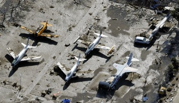 Japanese vintage military planes have dirt on their wings at Matsushima air base of the Japan Air Self-Defense Force, northeastern Japan, on Saturday, March 12, 2011, one day after a giant quake and tsunami struck the country's northeastern coast. (AP Photo/Kyodo News)  MANDATORY CREDIT, NO LICENSING ALLOWED IN CHINA, HONG  KONG, JAPAN, SOUTH KOREA AND FRANCE