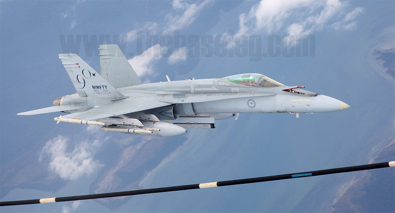 Royal Australian Air Force F/A-18A Hornet A21-48 in a scheme commemorating the RAAF's 90th Anniversary scheme slides across the underside of its tanker off Gippsland in Victoria to receive fuel. Note the tanker's refueling hose in the foreground