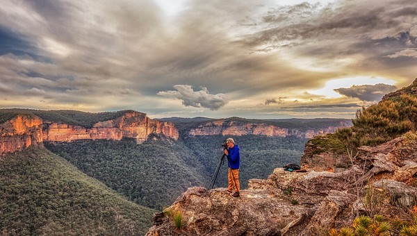 Tony Heyward standing on the edge of a cliff, photogaphing the Grose Valey, Blue Mountains, New South Wales.