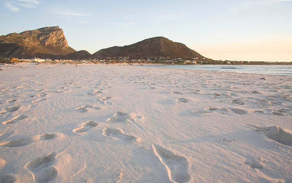 Footprints in the sand on Pringle Bay beach at sunset. Cape Hangklip looms in the distance