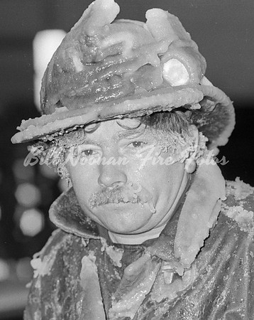 Firefighter covered with ice after a multiple alarm fire on Mercer Street in South Boston on a bitter cold March morning...