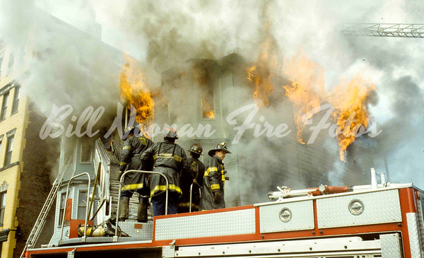 Large occupied frame dwelling on Adams Street in Roxbury...crew of Ladder Co. 4 in the foreground...