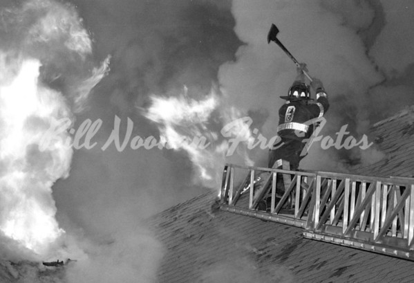 A Working Fire on Calendar Street, FF from Ladder Co. 29 opens the roof...fire was in a large 2.5 frame...circa 1989