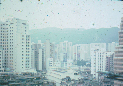 Any idea what these buildings are? This is outside our window at Causeway Bay. May be looking across Happy Valley? I am not sure. Most likely toward mid Causeway Bay.  Mutsukoshi (Sam Yuet) is not built yet. Aqua color is before Sogo. May be it was the new Excelsior Hotel. The hills are Dai Hang.