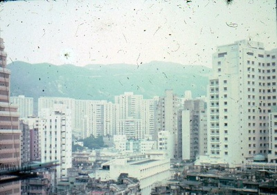 Any idea what these buildings are? This is outside our window at Causeway Bay. May be looking across Happy Valley? I am not sure. Most likely toward mid Causeway Bay.  Mutsukoshi (Sam Yuet) is not built yet. Aqua color is before Sogo. May be it was the new Excelsior Hotel. The hills are Dai Hang. May be this the the right orientation. Flip from previous picture. Then with this orientation, the aqua window building is Lee Garden  Hotel. Then this is outside the bedroom window.