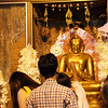 mashing gold leaf onto the buddha