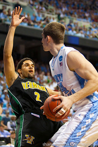 Luke Apfeld (2) of Vermont draws a charge on Tyler Zeller of North Carolina during the Second Round of the NCAA National Tournament at Greensboro Coliseum in Greensboro, NC on Friday, March 16, 2012.