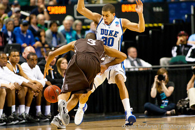 Seth Curry (center) of Duke draws a charge on C.J. McCollum of Lehigh during the Second Round of the NCAA National Tournament at Greensboro Coliseum in Greensboro, NC on Friday, March 16, 2012.  #15 seeded Lehigh upset #2 Duke to advance on to the Third Round.