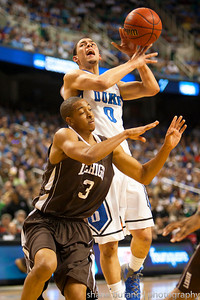 Austin Rivers (center) of Duke is fouled by C.J. McCollum of Lehigh on his way to the basket, during the Second Round of the NCAA National Tournament at Greensboro Coliseum in Greensboro, NC on Friday, March 16, 2012.  #15 seeded Lehigh upset #2 Duke to advance on to the Third Round.