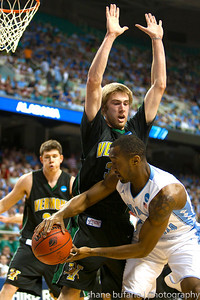 Matt Glass (center) of Vermont plays tough defense on North Carolina's Justin Watts during the Second Round of the NCAA National Tournament at Greensboro Coliseum in Greensboro, NC on Friday, March 16, 2012.