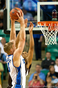 Mason Plumlee (left) of Duke dunks over C.J. McCollum of Lehigh during the Second Round of the NCAA National Tournament at Greensboro Coliseum in Greensboro, NC on Friday, March 16, 2012.  #15 seeded Lehigh upset #2 Duke to advance on to the Third Round.