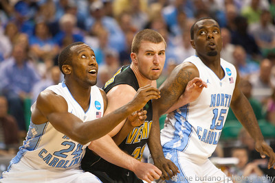 Brian Voelkel (center) of Vermont boxes out Justin Watts (left) and B.J. Hairston (right) of North Carolina during the Second Round of the NCAA National Tournament at Greensboro Coliseum in Greensboro, NC on Friday, March 16, 2012.