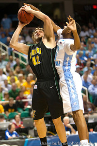 Ben Crenca (left) of Vermont is blocked by North Carolina's James Michael McAdoo during the Second Round of the NCAA National Tournament at Greensboro Coliseum in Greensboro, NC on Friday, March 16, 2012.