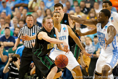 Sandro Carissimo (center) of Vermont passes out of the tough defense of Kendall Marshall during the Second Round of the NCAA National Tournament at Greensboro Coliseum in Greensboro, NC on Friday, March 16, 2012.