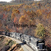 """November 4, 1978 - what a glorious day.  Temperature around 70 degrees, bright sun with a few cirrus clouds scattered about, trees a bit past their prime, but still spectacular.  And here you are, sitting above a cut between Camp Two and First Rocky tunnel on the Clinchfield Loops, a place dear to your heart.  Could it get any better?  Sure - how about a train.  And as if on cue, the magical rumbling suddenly emits from high above the Ridge.  It continues as the train winds around the big loop.  As the train grows ever closer, the whine of the dynamic brakes overwhelms the rumble of the wheels as the CRR SD40, SCL SD45 and two CRR GP38-2s fight to hold back the force of gravity on the 1/2% grade.  The coal train passes, the whine of dynamics fade, the rumble echoes off the ridges.  Well, it don't get much better than this!""  Photo & caption quote by Chapter member Tom Blackwell."
