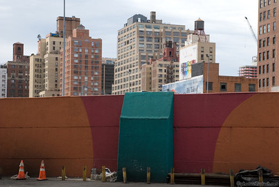 a colorfull wall in New York City helps to frame the skyline  behind.