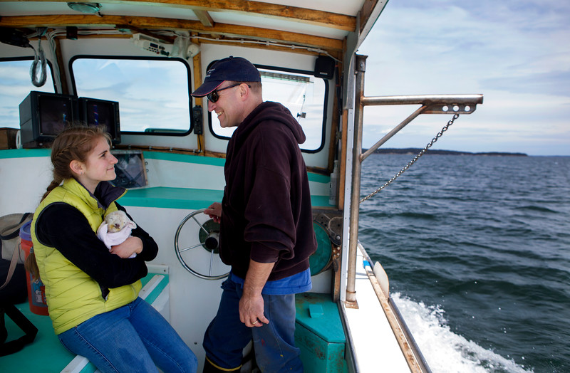 NASH ISLAND, Maine -- 05/17/2017 - Alfie Wakeman (right) smiles at his daughter, Evie Wakeman, 15, while heading back to the wharf with an abandoned lamb found on Little Nash Island Wednesday. The family takes care of approximately 150 sheep spread between Little and Big Nash Islands. Ashley L. Conti | BDN