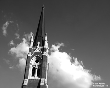 The steeple of First Baptist Church with the cloud peeking through a cloud behind it.