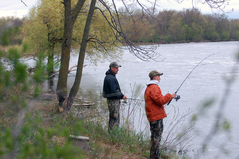 Father and son fish for walleye on the east shore of the Mississippi, south of campus.