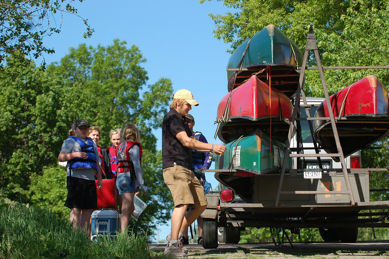 Outdoor Endeavors worker unloads canoes at the landing south of campus.