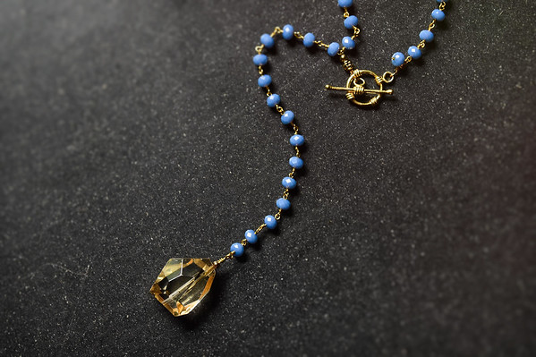 Long blue beaded lariat, smokey topaz pendant, front gold toggle clasp