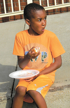 Jaheir Johnson, 6, munches on a hot dog during the fifth-anniversary celebration for The Neighborhood Pantry at Church of Genesis. He attended with Thleatha Price and Isaac Williams.<br /> — Dan Irwin
