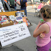 Margaret Feil, 8, enjoys a sno-cone while examining the Columbia Gas backhoe packed with food and other household supplies. — Dan Irwin