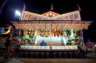 "Ball & pony show | Roll-a-ball taught me one valuable lesson as a kid: only play select carnival games, especially late in the evening. I guess it's not that valuable a lesson, but it's still one I learned. This is one of the few games where you play against other people rather than against the game itself. If you play late in the evening, when you have fewer opponents, you have a better chance of picking up a prize. Really, though, why would you want one of those stuffed monstrosities?  Moving along, the guy in the blue shirt presiding over the Roll-a-ball horse races is Bob. He gave me a hard time about taking photos of his stand, but it was all good-natured banter. ""Is this gonna be on the internet?"" He asked. Yes. He laughed sarcastically as if to approve but feign disinterest. Bob is very good at his job – playfully needling people to entice them to play. You can tell he was a former radio disc jockey or something along those lines and is very, very quick on his feet. There's a reason he's on the microphone. I had fun listening to him. Hopefully Bob remembers where to find his picture."