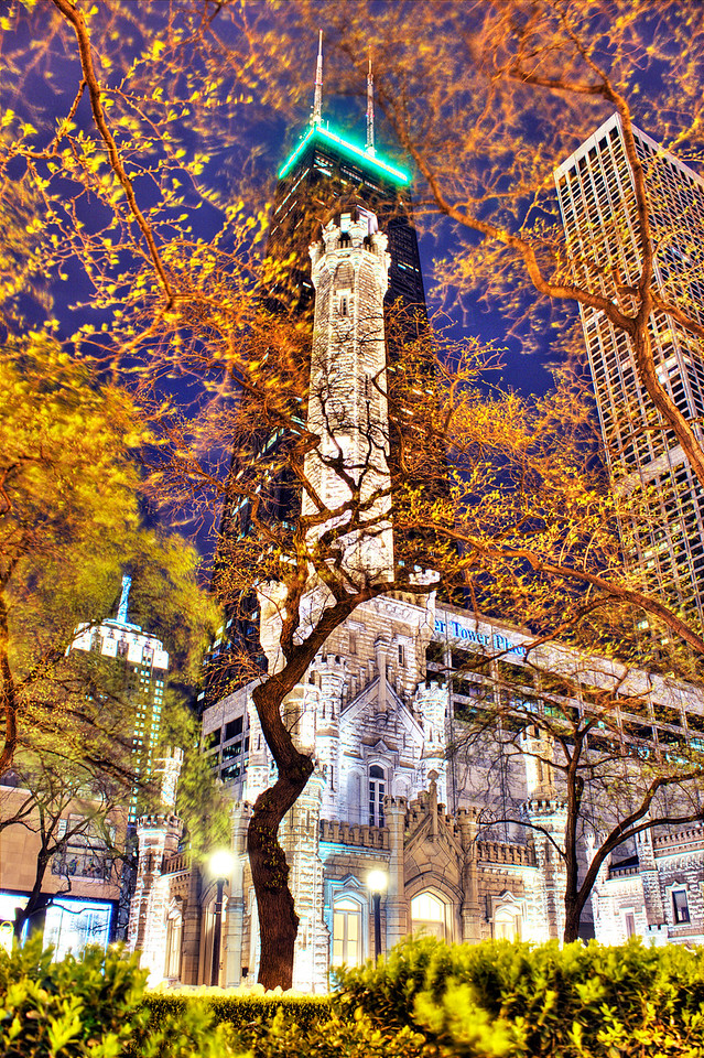 "The Hancock over Water Tower | The Chicago Water Tower is the only public building in the ""burn zone"" that survived the Chicago Fire of 1871. Ever since, it's been considered a symbol of Chicago's past and phoenix-like rise to Global City. While developments like the massive Hancock building have overtaken the water tower in size, it's stature is still quite great in Chicago. This photo was taken on a very windy night, which sometimes makes taking HDR images very challenging. In this instance, however, the blurring of the trees' branches creates a kind of chaotic framework around two of the city's most treasured landmarks."