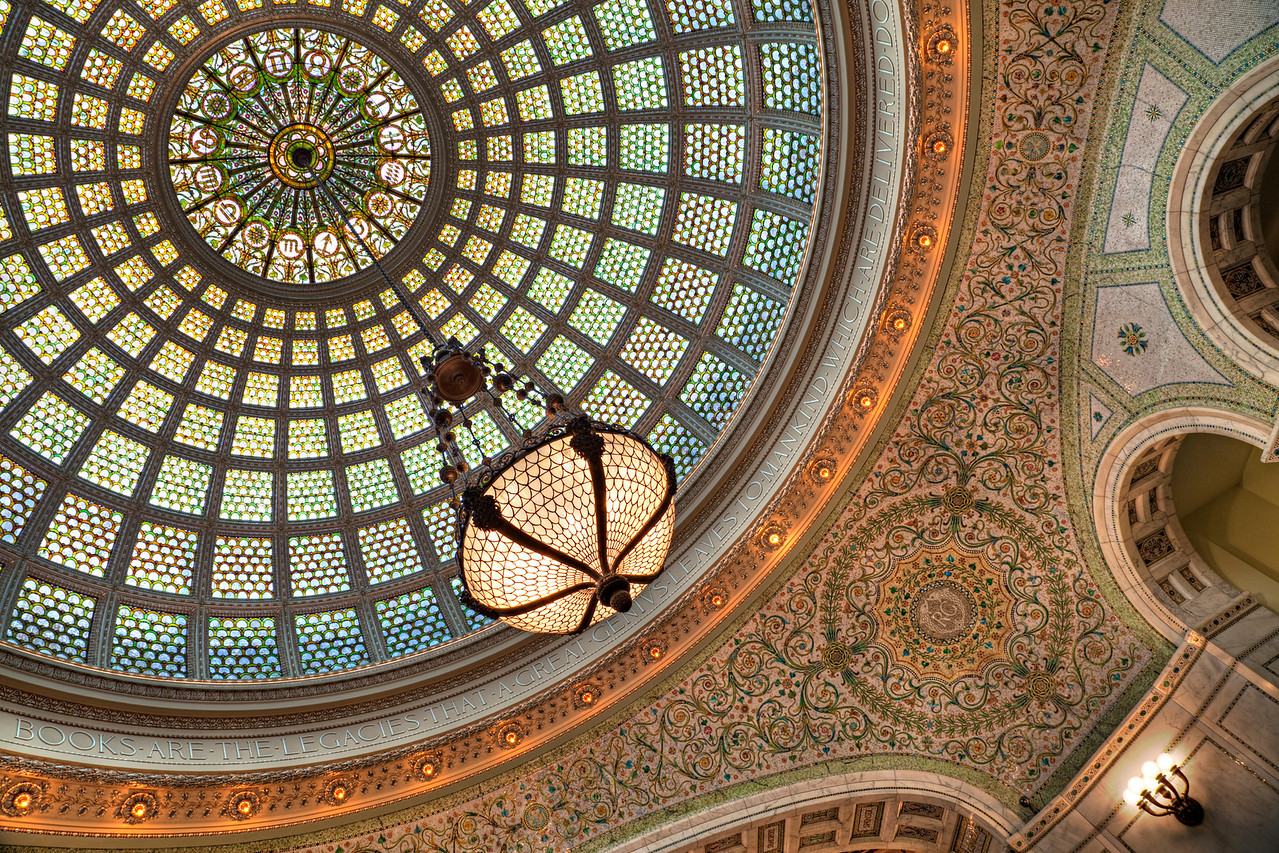 "The domed ceiling | Inside the Chicago Cultural Center's south end is a gorgeous room detailed to the tiniest degree. I'm stumped for words to even start describing it. Honestly, the picture says enough to display both the room's beauty and grandeur. I framed it this way so the hanging light comes right at you as it does in person. The color and light force your attention upward through the rotunda. It's amazing.  When I was a little boy I saw a performance of Mr. Rogers Neighborhood, a local PBS show, in this very room. I think Lady Aberlin's dress was blue and Mr. Rogers' cardigan gray. Somehow, I remember going ""back stage,"" which was just a side door into a stairwell. I remember nothing of the performance, but at the time I did think the room was a bit elaborate for Mr. Rogers."
