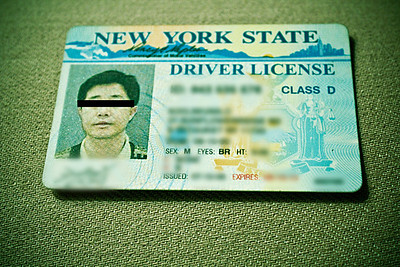 "My new fake ID | I recently purchased a Canon 5D Mark II. I opened the package from UPS, because it looked right. The camera box also looked right, so I opened that. Once inside the first flap, however, it started to look wrong. There was a pink post-it note with ""The battery is inside the camera, thanks"" scrawled rather legibly — but any scrawling at all on a post-it note on a would-be new camera box is rather wrong. That's red flag number one. Inside, I found the battery packaging open, some other packaging open and creases in the warranty paper work. That's red flag number two. Also, I found no packaging receipt.  Red flag number three was very interesting. Noticing that the camera itself looked to be in perfect shape, I decided to turn it on – after all, whomever left the pink note had already left the battery in the camera. It turned on. The screen displayed a message in Korean. Everything was in Korean. Everything. The menus were in Korean, so I had to use my other Canon to match up the menus and figure out how to place the camera into English (which it should have been factory) and continue problem solving. I decided to open the manual to see if anything else was off with this particular camera… and that's when this driver's license fell out and onto the floor.   The license sat there at my feet for a few seconds as I stared at this development in disbelief. Fearing that my camera was not in fact new, or perhaps even hot, I called the seller to rectify the situation. After three phone calls with them and a visit from the local police to search the guy's ID for a police record and the camera's serial number to see if it was reported stolen (this was encouraged by the seller), everything came back clean. It turns out my camera was probably a return that got mixed up in shipping and sent out as ""new,"" which it certainly was not.  My new new camera arrived rush delivery a day later. I received a $50 credit for future purchases from the seller, and I shipped back the bogus ""new"" camera once the new new camera was in my possession. I'll be reimbursed for the mailing costs. In the end, I've also acquired a great new fake ID – which looks nothing like me – and expires a few years from now.  Why this ID was in the box remains a mystery. I'm tempted to mail it to the man who obviously lost it, but I'm almost certain he's gotten himself a new ID by now. I'm tempted to keep it as part of a very strange story. The police said I could. I took the photo of the ID with my Canon T3I while waiting for the second 5D Mark II."