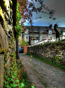 Ambleside row houses | A name like Ambleside suggests a walking community, and with around 3,000 inhabitants this English hillside town at the top of Lake Windermere in Cumbria is exactly that. Built up on top of itself, Ambleside offers spectacular views of the picturesque Lake District. This little row of cottages near the town center is typical dwelling in Ambleside. Stone walls, gravel drives and color adorn most everything. It would be quite a challenge to find any area of the UK more quaint and beautiful than the Lake District. This photo, taken on a point-and-shoot, is three exposures and hand-held against the stone.