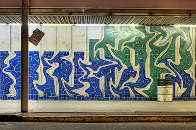 "Bus stand graffiti tile | I don't often manipulate my photographs beyond the application of HDR and some relatively minor touch-ups. This is different. I like the stark minimalism of the original, but having known some very talented graffiti artists from my college days, this looked like the perfect place for them to do their work. The two photos below are the exact same photo, but the second is ""liquified"" via Photoshop to achieve the warped look on the tile. Hanging out with my friends, I decided if I was ever a graffiti artist my tag would be the word ""Left"" for myriad reasons, but mostly because you could play with it in so many ways. Here I decided to yank on these tiles rather than leave my tag. Anyway, the shot was taken at a bus stand on a narrow strip of Chicago property that connects O'Hare Airport to the city proper. I guess if Chicago can get away with that I can toy with the outcome of the photo as I please."
