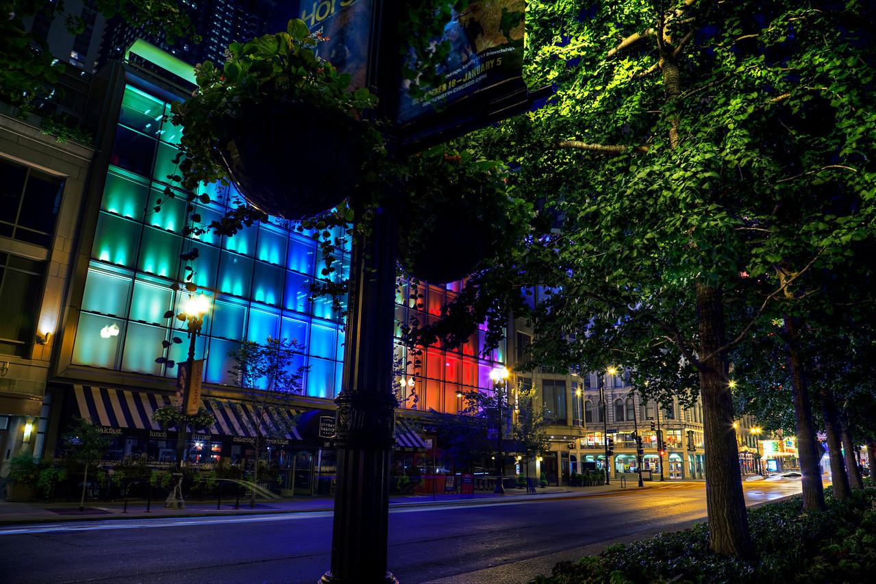 Color wall | The colors change and bounce around. Sometimes they fade in and out. I've tried to capture this scene in transition several times, but shooting the facade of the building straight-on doesn't do much for me. It took placing trees in the composition to truly draw out the dynamic, bold color. This is the Randolph side of the building that houses the Goodman Theatre, and these windows are actually peoples' offices. I've never seen anyone here working late. I'd imagine getting things done before the distraction of the light show is paramount!