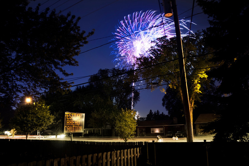 When fireworks come to you | I don't have to travel too far to enjoy the fireworks. They're right outside my back door. Of course that means there's a festival a few blocks away, and someone parks their car in a way that nearly blocks your driveway, and they walk through your lawn, because, well, just because.  Halfway through the fireworks display I pulled a table out into the yard and got my ladder out of the garage. I placed my tripod on the table and telescoped the head as high as it could go. My camera stood about 8 1/2 feet off the ground for this shot, so I had to climb 3/4 of the way up the ladder just to reach it. I fired off about 50-60 shots of the fireworks, but this image is comprised of just four. Long exposures are great for capturing everything but the finale, which photographs best in shorter bursts. This photo happens to be part of the middle of the display. When you're standing there watching, everything between you and the fireworks kind of melts away to the point that you don't even notice the trees and power lines. I decided to leave them in so you can see my cluttered but outstanding view. Stay off my lawn and out of my driveway, OK?