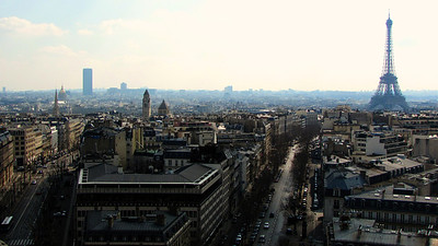 Parist to the southwest from Arc de Triomphe | To me, the Eiffel Tower seems like the worst way to see Paris. Why remove the city's greatest landmark from your vantage point in order to find an above-the-city perspective? The Arc de Triomphe's roof, 164 feet (50 meters) above street-level serves as a magnificent stage for photographing La Ville-Lumière. This photo, from a point-and-shoot Canon SX120 IS, keeps the city's anchor in frame. The white wall of clouds almost acts as a curtain with blue haze separating the foreground from the photo's background. The hint of a pastel sky pays homage to Rococo.