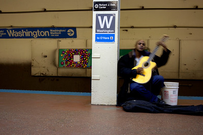 "The blue line guitarist | I wonder how many people are like me on this one. Whenever I head into a subway in any city – be it Chicago, New York, London, Paris or Washington D.C. – I hope to hear street musicians. There's this anticipation as you head for the initial descent that you might hear something special in the grungiest of places. The notes echo up quietly from inside the cavern of the tunnels and only grow warmer and louder as you draw near. It's this perfect mix of curiosity for what's to come and enhancement of setting. The street musicians make waiting for a train bearable with the beautiful melodies they bounce off those decrepit walls of darkness.  This particular guitarist, I believe, is Chris. He's really nice to me, and we talk almost every time I see him. He always welcomes me taking his photo and I made a video of him once, too. I think Chris doesn't mind the attention, because I don't hurt his ""sales."" People tend to walk up and drop money in his bucket when I start taking photos, but it's nothing that I'm doing. They really like Chris's music. I think I'm just an icebreaker for them. Chris's notes spill off his guitar and climb and fall like a haunted organ in the great hall of the mansion in Edward Scissorhands. He's truly a fun listen. I keep telling Chris that I need to get him a copy of this photo. It sums him up completely as he's always in motion and so focused on the music. If you ever see Chris, make sure to drop a dollar in his bucket and tell him he can download his photo from this site. It's been a while since we've bumped into one another."