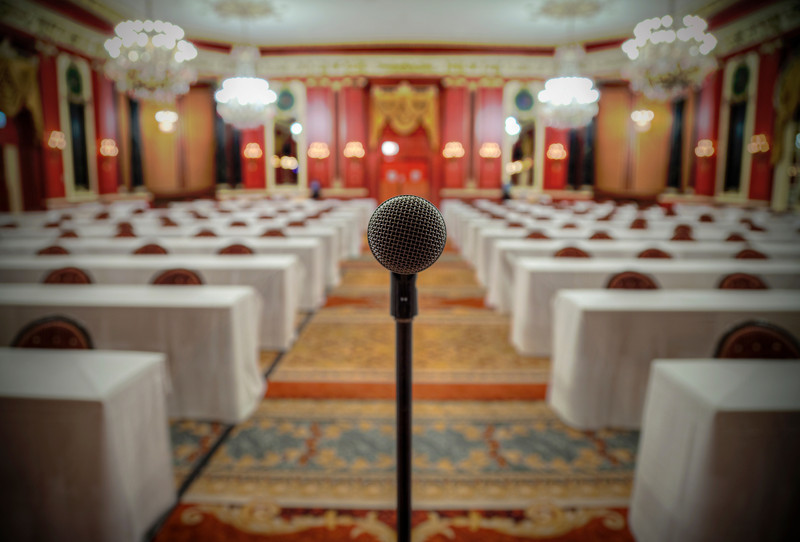 The open mic | Given free reign of an old Chicago hotel recently, my favorite discovery occurred just before midnight in a massive red ballroom. The microphone not only stood perfectly alone front and center, it was also left on. I remember speaking into it moments before taking the picture. My words echoed around the mostly empty room, but I don't have any idea of what I said. Concerned I'd stir security with taking my exploration a step too far, I quickly snapped off six exposures of the microphone looking directly into its head. Three of them were used to make this photo.  I wasn't the only one in the room. Two children were running around playing as if they owned the place while their mother watched carefully that they keep in line. It was a surreal moment to be in this incredible room with kids playing as the day closed. We made sure to take a picture of the kids that I'll hope to get posted in the near future. I liked how the microphone was left there waiting for a voice. It became the entire focal point of the gigantic space.