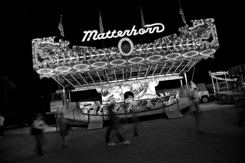 Anti Matterhorn | In the waning hours of its final night the carnival ceases to exist on its own. It is Sunday night and despite a hard close at 11 o'clock the people migrate away from the flashing lights and the color of the event into the surrounding darkness prior to deadline. This leaves an unsettling feeling that the festival is dying a premature death. The band's energy from the corner of the park no longer pulses through the crowd. It now blares over the drone of the whirring rides and fewer, lesser voices. The rides grow more and more vacant. People pass them as if the fun has washed away. The Matterhorn no longer matters.