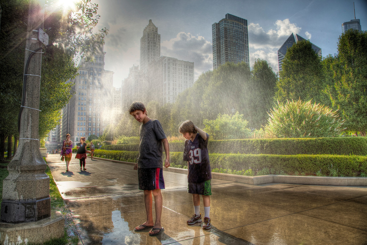 Cooling off | Bonus day – two photos, less type. I was told by one person that they like my writing on these posts, but two people said I should limit my words. I'm not sure how I feel about this, but I'm going to keep it short today.  These boys are from Argentina. It was 99 degrees. They stood under a hose attached to a streetlight. The second image was actually taken prior to the first. There are a few different ways to discern this. Maybe you can find one.