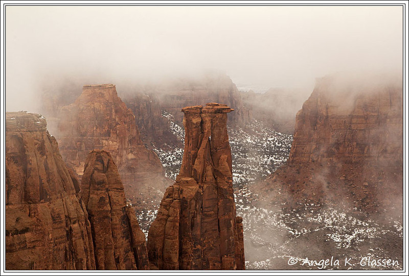 Fog moves in and out of Monument Canyon in Colorado National Monument, almost hiding Independence Monument (left center) while Kissing Couple (front center) remains clearly visible
