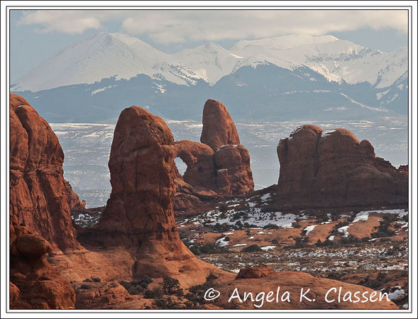 Turret Arch and other sandstone formations stand outlined against the La Sal Mountains close to the Windows section in Arches National Park